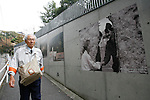 Nov 10, 2009 - Tokyo, Japan - A Japanese man walks past large pictures depicting the collapse of the Berlin Wall along the wall of the German Embassy in Tokyo.