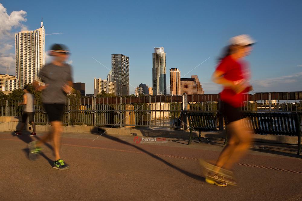 Joggers run on the Lamar Street Pedestrian Bridge over the Lady Bird Lake overlooking the Austin Skylkine