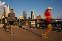 Joggers run on the Lamar Street Pedestrian Bridge over the Lady Bird Lake overlooking the Austin Skylkine