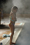 Girl in bathing suit shivers on the steamy deck of an outdoor pool in winter.