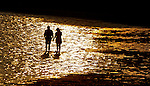 Two lovers walk though the shallow water as the sun sets at Shell Point in Wakulla County, Florida south of Tallahassee.