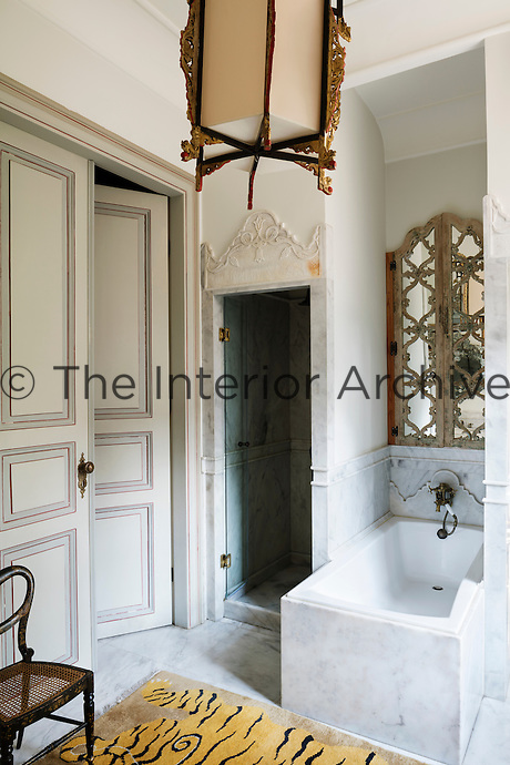 In the bathroom, above the marble bath, the mirror is inlaid with mother of pearl.