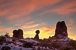 A colorful winter sunset with Balanced Rock in silhouette in Arches National Park, near Moab, Utah, USA.