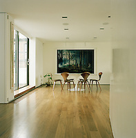 The dining room is simply, but stylishly furnished with an Eero Saarinen table and chairs. A photograph by Gregory Crewdson adorns one wall.