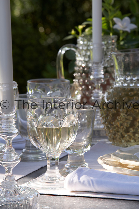 A table is laid for lunch in the garden with antique glassware and glass candlesticks