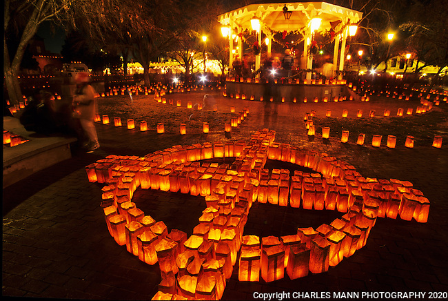 Hundreds of bright faralitos, each a paper bag containing a candle, suggest a Zia symbol during the Christmas Eve celebration on the plaza in Old Town in Albuquerque, New Mexico