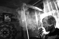 """Nagorny-Karabach, 10.05.2011, Shushi. Unter dem Portrait seines im Krieg gefallenen Bruders raucht ein junger Mann eine Zigarrette. """"The Twentieth Spring"""" - ein Portrait der s¸dkaukasischen Stadt Schuschi, 20 Jahre nach der Eroberung der Stadt durch armenische K?mpfer 1992 im B¸gerkrieg um die Unabh?ngigkeit Nagorny-Karabachs (1991-1994). A young man smokes a cigarette sitting under a portrait photo of his brother who fell during the civil war.""""The Twentieth Spring"""" - A portrait of Shushi, a south caucasian town 20 years after its """"Liberation"""" by armenian fighters during the civil war for independence of Nagorny-Karabakh (1991-1994)..Un jeune homme fume une cigarette, assis sous un portrait de son frère tombé pendant la guerre civile.""""Le Vingtieme Anniversaire"""" - Un portrait de Chouchi, une ville du Caucase du Sud 20 ans après sa «libération» par les combattants arméniens pendant la guerre civile pour l'indépendance du Haut-Karabakh (1991-1994)..© Timo Vogt/Est&Ost, NO MODEL RELEASE !!"""