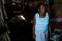 A Colombian woman, a shellfish picker working in the mangrove swamps, stands inside her wooden house in a stilt house area close to Tumaco, Colombia, 15 June 2010. Deep in the impenetrable labyrinth of mangrove swamps on the Pacific seashore, hundreds of people struggle everyday, searching and gathering a tiny shellfish called 'piangua'. Wading through sticky mud among the mangrove tree roots, facing the clouds of mosquitos, they pick up mussels hidden deep in mud, no matter of unbearable tropical heat or strong rain. Although the shellfish pickers, mostly Afro-Colombians displaced by the Colombian armed conflict, take a high risk (malaria, poisonous bites,...), their salary is very low and keeps them living in extreme poverty.