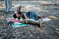 Mohammad Anwarul, a Bangladeshi homeless man plays with a street dog inside a public park in Dhaka, Bangladesh. Anwarul makes his living by collecting trash at the park.