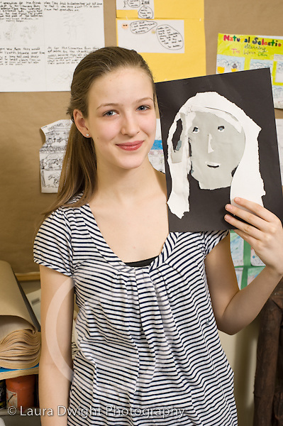 Education Middle School grade 8 art activity cut paper self portraits girl holding up art work and posing vertical