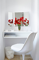 An Eero Saarinen Tulip chair is placed in front of a recessed dressing table shelf. A vase of vibrant red poppies in set in front of a vanity mirror.