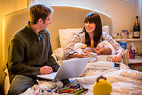 "A woman breastfeeding her 5 month old twins at the same time on her bed in her bedroom.  Her husband is sitting next to her working on his computer.<br /> <br /> Image from the ""We Do It In Public"" documentary photography project collection: <br />  www.breastfeedinginpublic.co.uk<br /> <br /> Hampshire, England, UK<br /> 11/02/2013"
