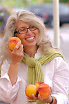 Mature woman holding peaches, smiling