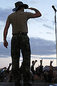 Country music star Tim McGraw salutes fans to show his appreciation for their service during a free concert for military and family members at Fort Carson, Colorado on May 21, 2003.  He put on the free concert to show appreciation for the military.