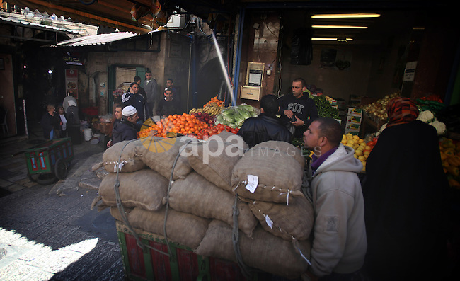 Palestinians shop at a street market in Jerusalem's Old City on February 12, 2014. Minister of Holy Places for the PA Mahmoud al-Habbash told Israel's Channel 10 network that the PA wants control of all the areas in Jerusalem that were won by Israel during the 1967 Six-Day War, including the Western Wall. Photo by Saeed Qaq