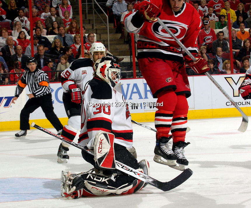 Carolina Hurricanes' Andrew Ladd jumps over a shot from teammate Tim Gleason (not shown) as the New Jersey Devils' goalie Martin Brodeur fails to make the save Thursday, March 15, 2007 at the RBC Center in Raleigh, NC. New Jersey won 3-2.