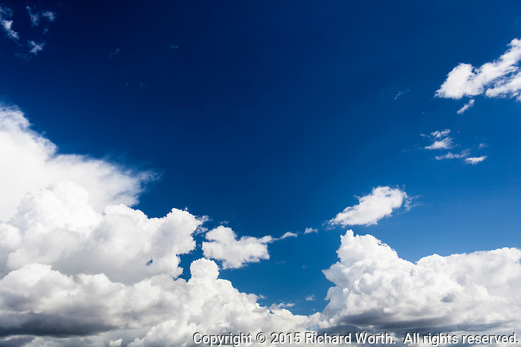 A deep blue sky at the top of the image is countered by storm clouds, puffy white above yet dark and threatening below.