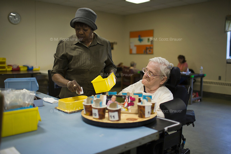 With the assistance of a caretaker, Fernald resident Margaret Rouleau sorts items for pay during work time at Site 7 at the Fernald Developmental Center in Waltham, Mass., USA.