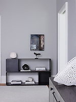 The master bedroom is decorated in soft greys and neutral giving the room a restful ambience. The console is by BDDW and an open unit displays books and sculptures.