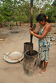 Aldeia Baú, Para State, Brazil. Kayapo woman using a large wooden mortar and pestle to crush babassu nuts with a sieve and an aluminium bowl of crushed nuts.
