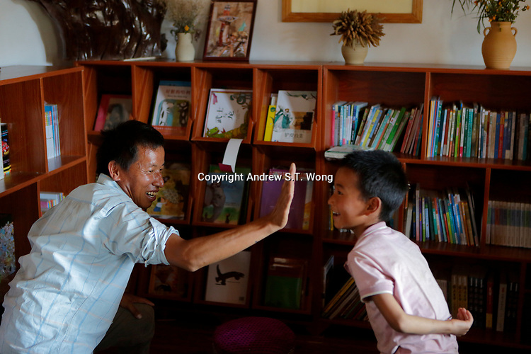 Wumu Village, Yulong County, Yunnan Province, China - Dongba priest He Jixian of the Naxi ethnic group teaches children from his village traditional Naxi culture during weekend school, June 2019.