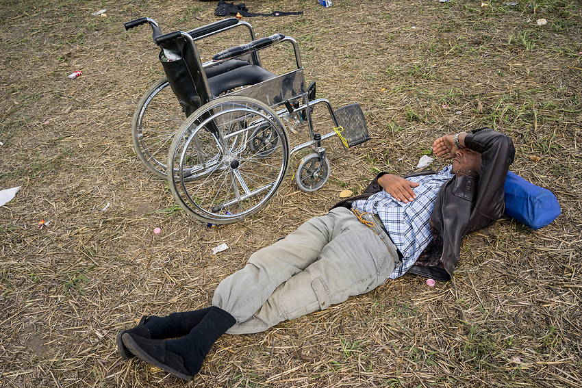 An elderly man rests near his wheelchair near the railway line that is used as a crossing point between Serbia into Hungary by mostly Syrian refugees. Refugees at Roszke Crossing on Serbian-Hungarian Border.