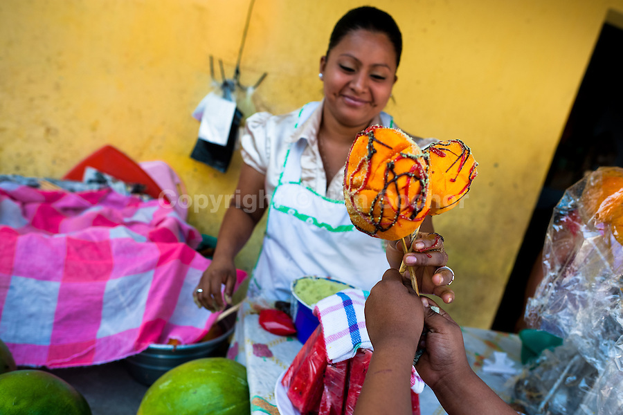"A Salvadoran woman sells mango with chocolate on a stick during the Flower & Palm Festival in Panchimalco, El Salvador, 8 May 2011. On the first Sunday of May, the small town of Panchimalco, lying close to San Salvador, celebrates its two patron saints with a spectacular festivity, known as ""Fiesta de las Flores y Palmas"". The origin of this event comes from pre-Columbian Maya culture and used to commemorate the start of the rainy season. Women strip the palm branches and skewer flower blooms on them to create large colorful decoration. In the afternoon procession, lead by a male dance group performing a religious dance-drama inspired by the Spanish Reconquest, large altars adorned with flowers are slowly carried by women, dressed in typical costumes, through the steep streets of the town."
