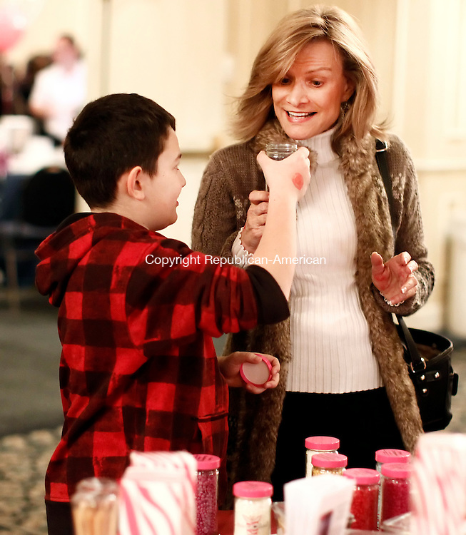 "Southbury, CT-03 February 2012-020313CM06-  Christian Diaz, 10, of Wolcott presents a vanilla musk candle from Pink Zebra, a soy candle and fragrance company from Cromwell, to his grandmother, Cathy Dalton during the 20th annual Chocolate Lovers' Expo to benefit Easter Seals, at the Crowne Plaza Hotel Sunday afternoon in Southbury.  The annual event featured a myriad of vendors, and included cakes, cupcakes, cookies, candies and gourmet specialty foods.  The event was held to help raise money for Easter Seals which provides ""exceptional services, education, outreach, and advocacy so that people living with autism and other disabilities can live, learn, work and play in our communities.""   Christopher Massa Republican-American"