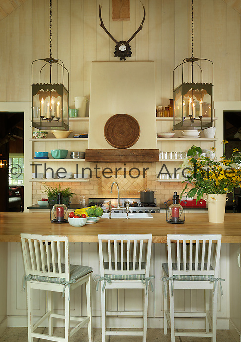A pair of lanterns hangs above the large kitchen island which also doubles as a breakfast bar