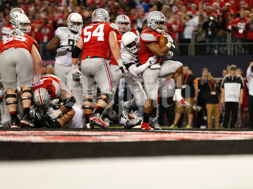 Ohio State Buckeyes running back Ezekiel Elliott (15) breaks through the Oregon Ducks defense for the final touchdown of the game in the fourth quarter of the College Football Playoff National Championship between the Ohio State Buckeyes and the Oregon Ducks at AT&T Stadium in Arlington, Texas, Tuesday afternoon, January 13, 2015. The Ohio State Buckeyes defeated the Oregon Ducks 42 - 20. (The Columbus Dispatch / Eamon Queeney)