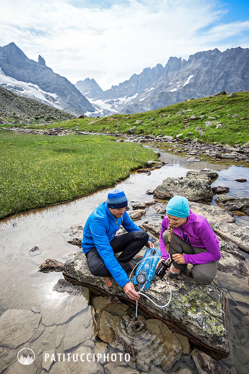 Filtering water in a mountain creek while backpacking in the Swiss Alps