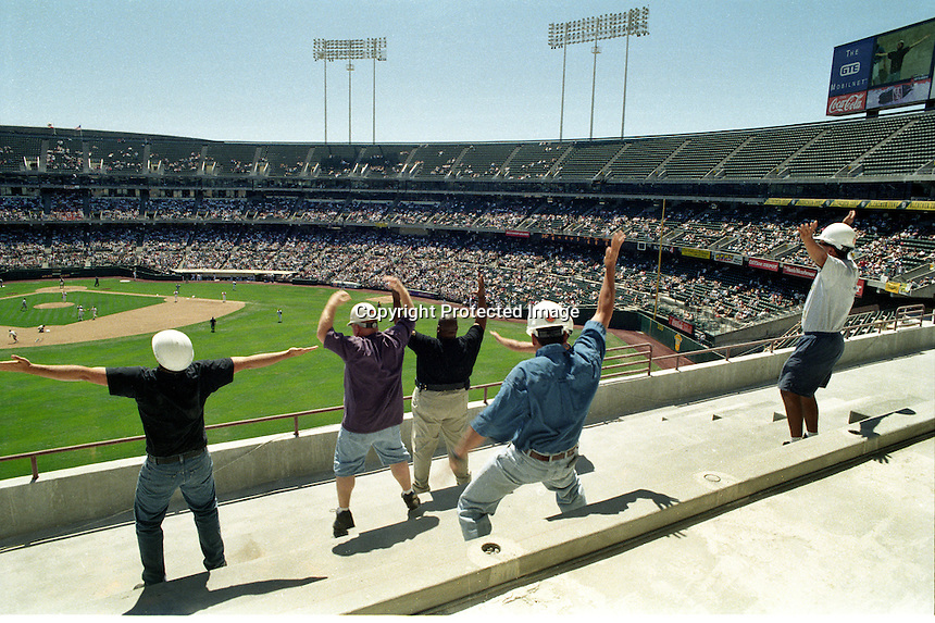 "Oakland Alameda County Coliseum: Construction workers do a ""Y.M.C.A."" dance in the left field stands between inning of the Oakland Athletics game. The Coliseum was under going expansion construction for the return of the Oakland Raiders. The A's started the 1996 season in Las Vegas for a few games while the stadium construction was finished..The A's opened in Las Vegas."