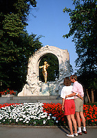 A tourist couple looks at the monument to Johann Strauss. Vienna, Austria.