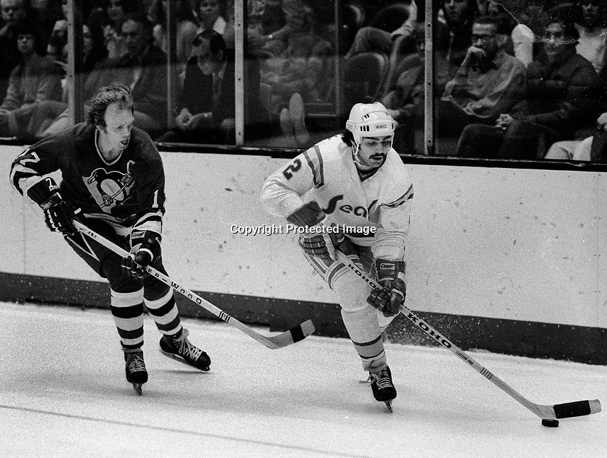 Seals Rick Hampton with Pittsburg Penguins Ron Schock..(1975 photo/Ron Riesterer)