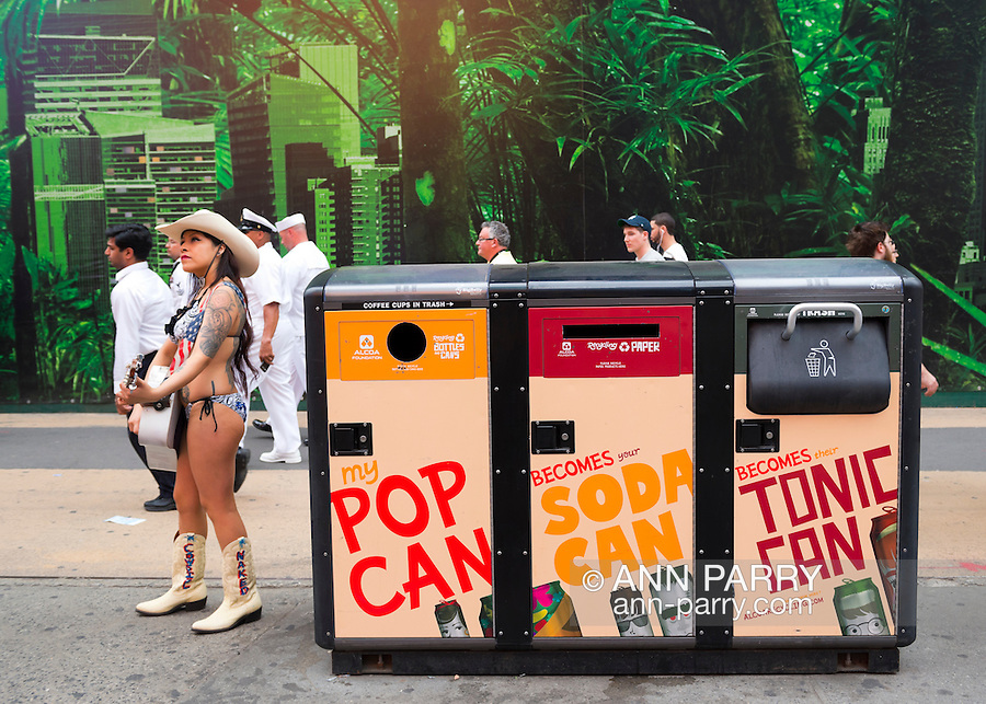 Manhattan, New York, U.S. - May 21, 2014 -  In Times Square, a young woman wears a bikini, cowboy hat, and cowboy boots with Naked Cowgirl written on them, as she plays guitar next to the solar powered 3 bin recycling system, for plastics, bottles and cans, and trash, during a pleasant Spring day in Manhattan. Several pedestrians behind her are uniformed members of the US Coast Guard.