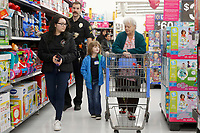 NWA Democrat-Gazette/DAVID GOTTSCHALK Mayely Guillen (from left), a junior at Springdale High School and member of the Law and Public Safety Academy, and Officer Ethan Mast, with the Springdale Police Department, shop Tuesday, December 4, 2018, with Gracie Shankel, 5, and her great grandmother Barbara Snodgrass at the Walmart Supercenter on Pleasant Street in Springdale. More than 200 children participated in the Springdale Police Department Shop with a Cop program. The department collected $45,000 this year for the program.