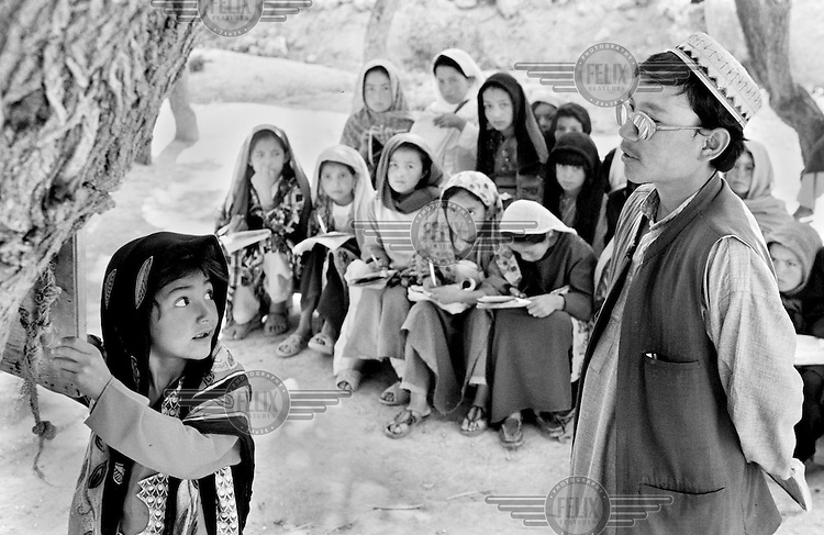 An ethnic Hazara girl writes on a blackboard hanging from a tree in an improvised outdoor classroom near Bamiyan, Afghanistan on June 29, 2002. Girls are now allowed an education for the first time since before the rule of the Taliban, but the only books available are islamic religious texts.