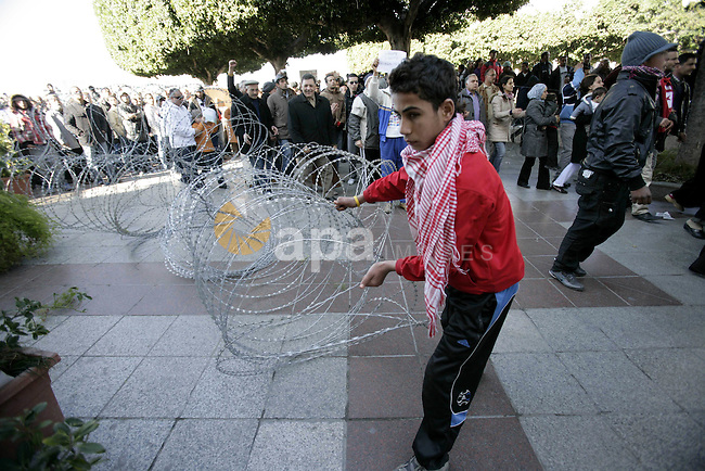 Tunisian protestors prepare to break into the barbed wire during a demonstration to demand a new government free of officials of the ousted regime of former president Zine el Abidine Ben Ali, in central Tunis, Tunisia, 23 January 2011. According to media reports, hundreds of people from throughout Tunisia started arriving on 23 January in the capital Tunis, as part of what was called a caravan of liberation . Tunisia marked its final day of a three-day mourning period for those killed in the weeks-long massive street protests on 23 January. Photo by Karam Nasser