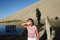 A girl stands infront of sand dunes near the tourist attraction Ming Sha Shan. Desertification is the process by which fertile land becomes desert, typically as a result of drought, deforestation, or inappropriate agriculture. 41 % of China's landmass in classified as arid or desert. Innapropriate farming methods and overcultivation have contributed to the spreading of deserts in China in recent years. Dunhuang, Gansu Province. China