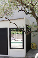 An outdoor swimming pool is located to one side of the terrace, glimpsed here through a black-framed window