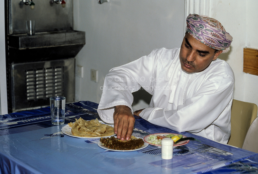 Nakhal, Oman.  Omani Eating Keema (meat, peas, beans) with his Hand.
