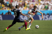 Thomas Muller of Germany takes on Patrice Evra of France