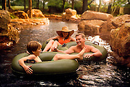 A family laughing and playing in Rambling River, a hotel pool.