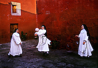 Novices play ball in the court yard during a break in their silence from the strict cloistered life in Santa Catalina Convent in Peru. Seven times during the day the young girls go to their chapel for chorus and pray, but once a day they play or sing in the garden. Among the 30 women who live in the convent are five novicias who study for five years to become a nun. The youngest is 15, the oldest nun is 98. <br /> <br /> They begin their day at Mass. Then the novicias have class and activities studying theology, music and the Bible. For their work, they embroider, make parsley soap, creams, cookies and iron. <br /> <br /> They never leave the premises unless they have special permission to go to the doctor and to vote. The founder accepted girls from the finest of Spanish families. The nuns today take the traditional vow of poverty.