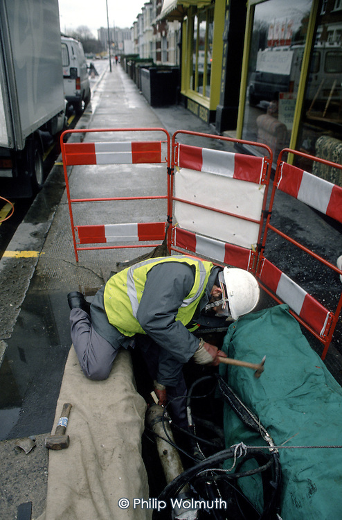 A telephone engineer carries out a  repair in Central London