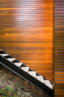 A series of wooden treads contained within a metal staircase ascends the side of the clapboard property