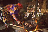 Old kuna woman preparing large pot of turtle over open fire, Comarca De Kuna Yala, San Blas Islands, Panama