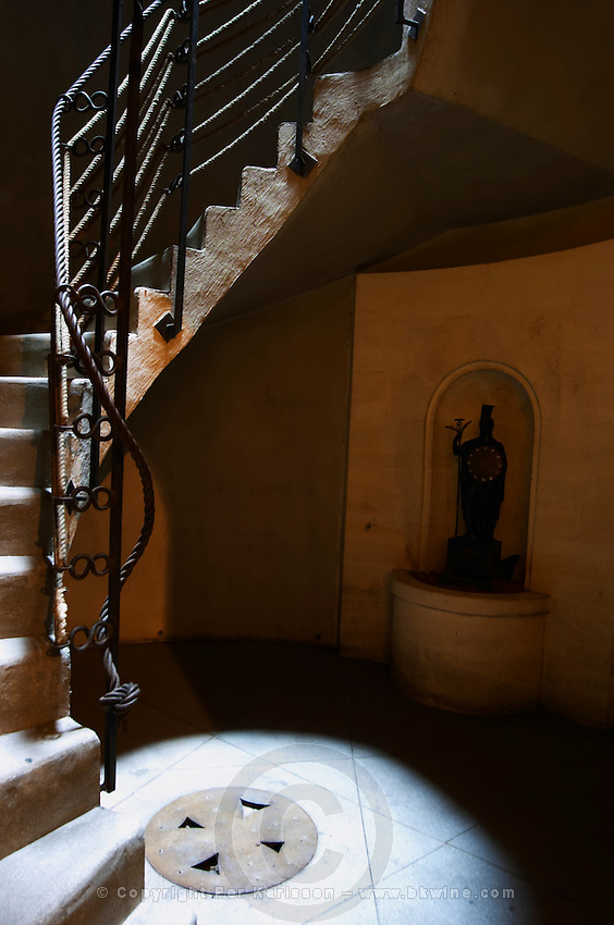 A flight of stairs in clairobscure with a ray of sunlight and darkness, a statue of Mercure Mercury the god of commerce. Chateau Romanin, Saint Remy de Provence, Bouches du Rhone, Provence, France, Europe