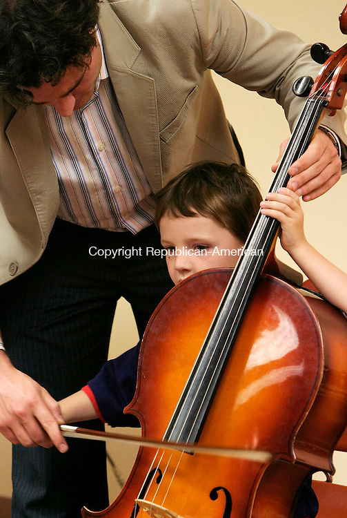 HARWINTON, CT - 25 MARCH 2005 -  052505JS05--Chris Speaker, 4 of Torrington, gets a lesson on a cello by Dan Trahey of the Hartford Symphony Orchestra's during an instrument zoo held Wednesday at the Harwinton Public Library. Students were allowed to try their hand on different instruments. The instrumnet zoo is part of the Musical Pathways education program of the Hartford Symphony Orchestra and sponsored by the Target Corporation. --Chris Speaker; Hartford Symphony Orchestra; Harwinton; Target, Dan Trahey are CQ