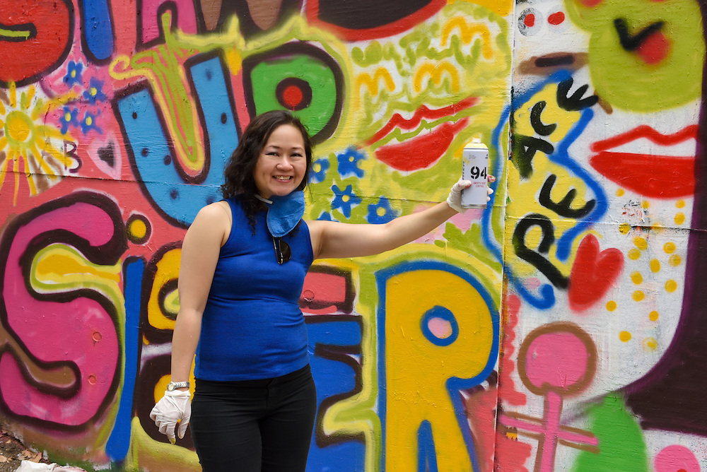 One of the artists proudly posing in front of the mural holding a can of spray paint.